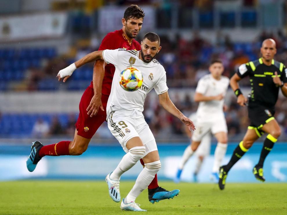 Benzema intenta marcharse del jugador de la Roma Fazio.