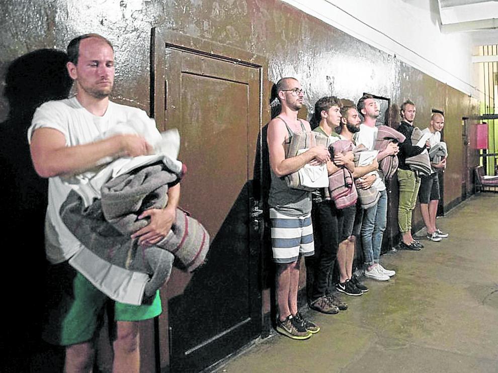 Unos turistas que se han atrevido a pasar la noche como reos son inspeccionados en la cárcel de Karosta por el oficial de turno.