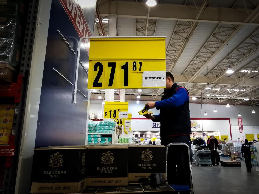 Un empleado cambia los precios ante la incierta situación económica argentina.