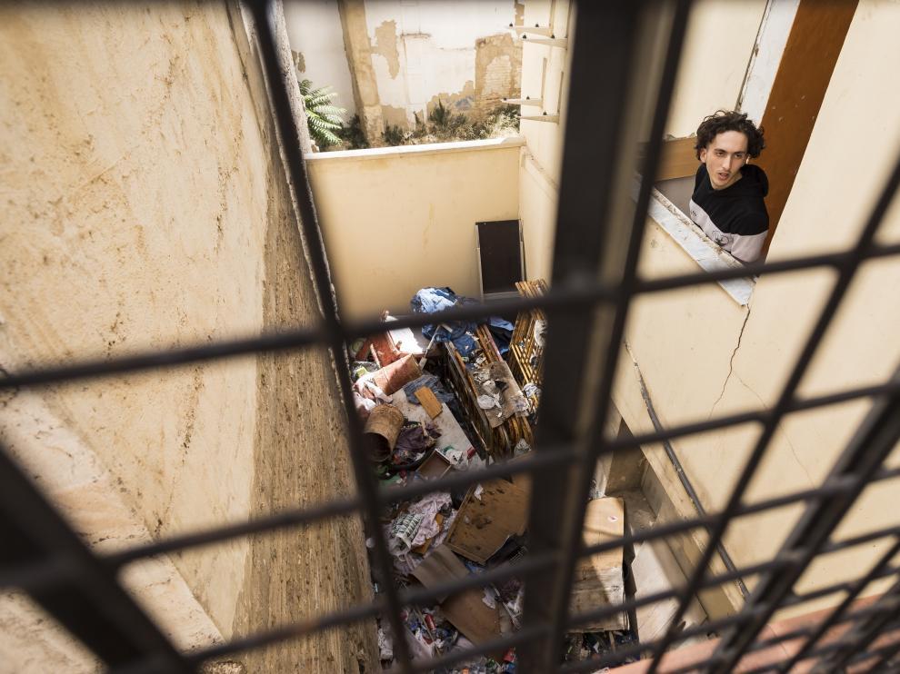 Uno de los jóvenes okupas conversa en el balcón con un vecino, en un patio de luces que se ha convertido en un insalubre vertedero.