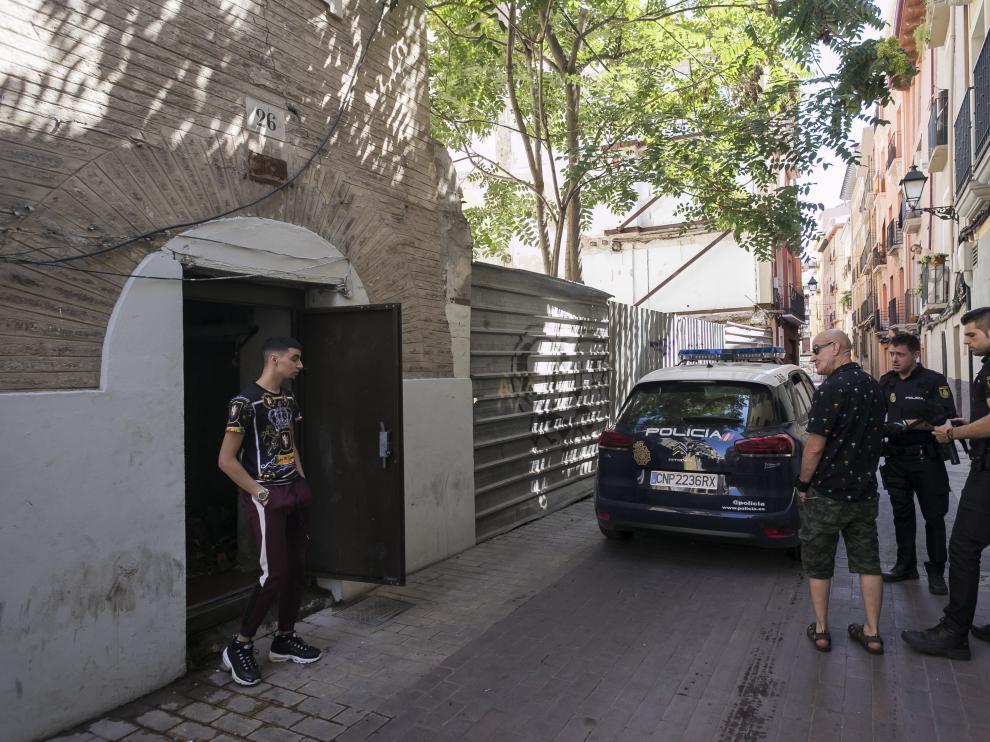 Dos policías nacionales y un vecino de la calle de Agustina de Aragón hablan con un joven okupa del edificio número 26.