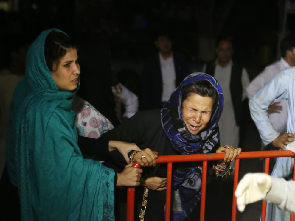 Una mujer llora mientras los servicios sanitarios atienden a familiares afectados por la explosión