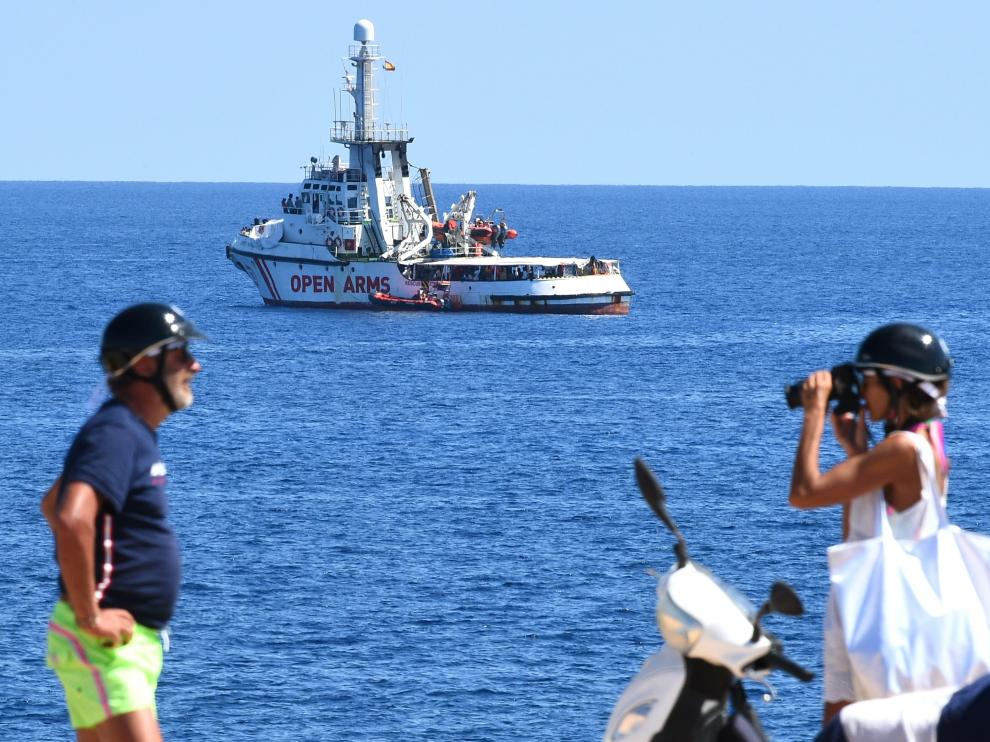 A man poses for a photo as the Spanish migrant rescue ship Open Arms is seen close to the Italian shore in Lampedusa, Italy August 18, 2019. REUTERS/Guglielmo Mangiapane [[[REUTERS VOCENTO]]] EUROPE-MIGRANTS/