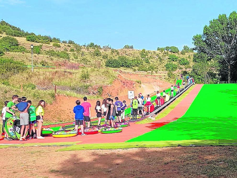 La pista de esquí sintética de Alcalá de la Selva y, a la izquierda, el tobogán para colchonetas.
