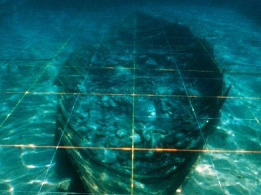 Imagen en la que pueden apreciar los restos de la nave fenicia cubiertos por la estructura metálica que se colocó para protegerla.