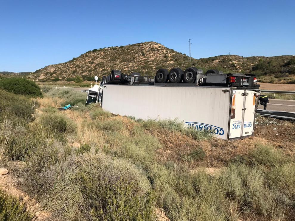 El camión ha quedado volcado en el arcén con las ruedas hacia arriba.