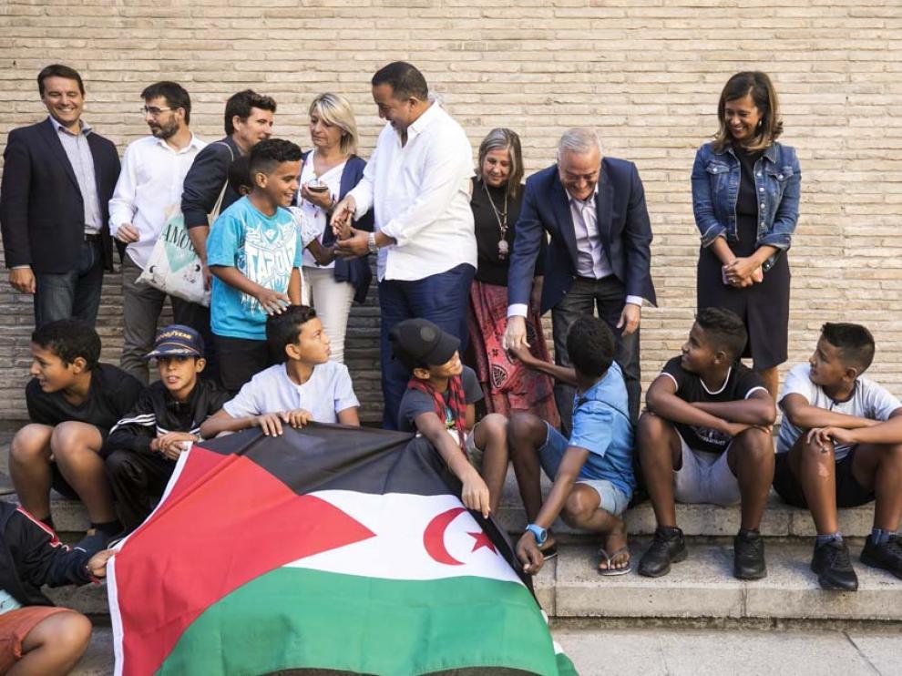 Varios niños saharauis charlan con políticos zaragozanos en el patio de San Martín de la Aljafería