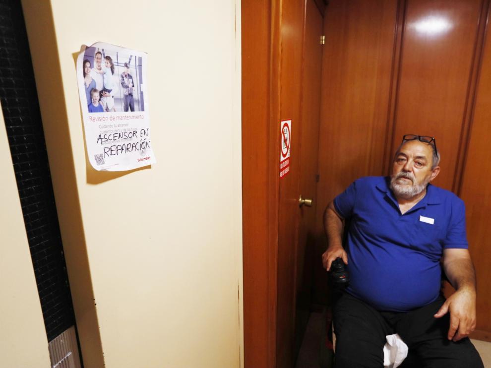 Jesús Luis Domínguez junto al cartel del ascensor estropeado en su edificio