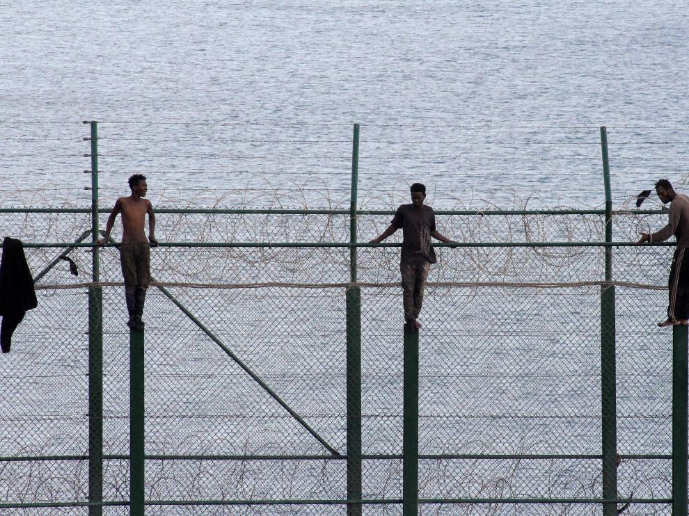 African migrants stand on a border fence as they attempt to cross into Spanish territories, between Morocco and Spain's north African enclave of Ceuta, Spain, August 30, 2019. REUTERS/Stringer NO RESALES. NO ARCHIVES [[[REUTERS VOCENTO]]] EUROPE-MIGRANTS/SPAIN-CEUTA