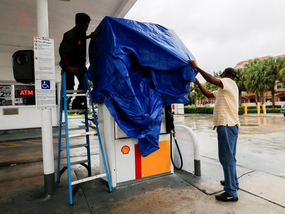 Workers cover a gas pump as the business closes ahead of the arrival of Hurricane Dorian in Boynton Beach, Florida, U.S., September 2, 2019. REUTERS/Joe Skipper [[[REUTERS VOCENTO]]] STORM-DORIAN/