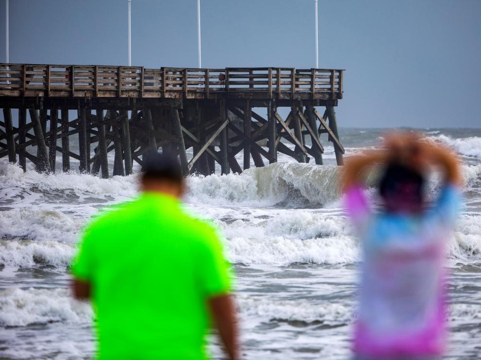 Unas personas contemplan la marea en la playa de Daytona, Florida, antes de la llegada del huracán Dorian.