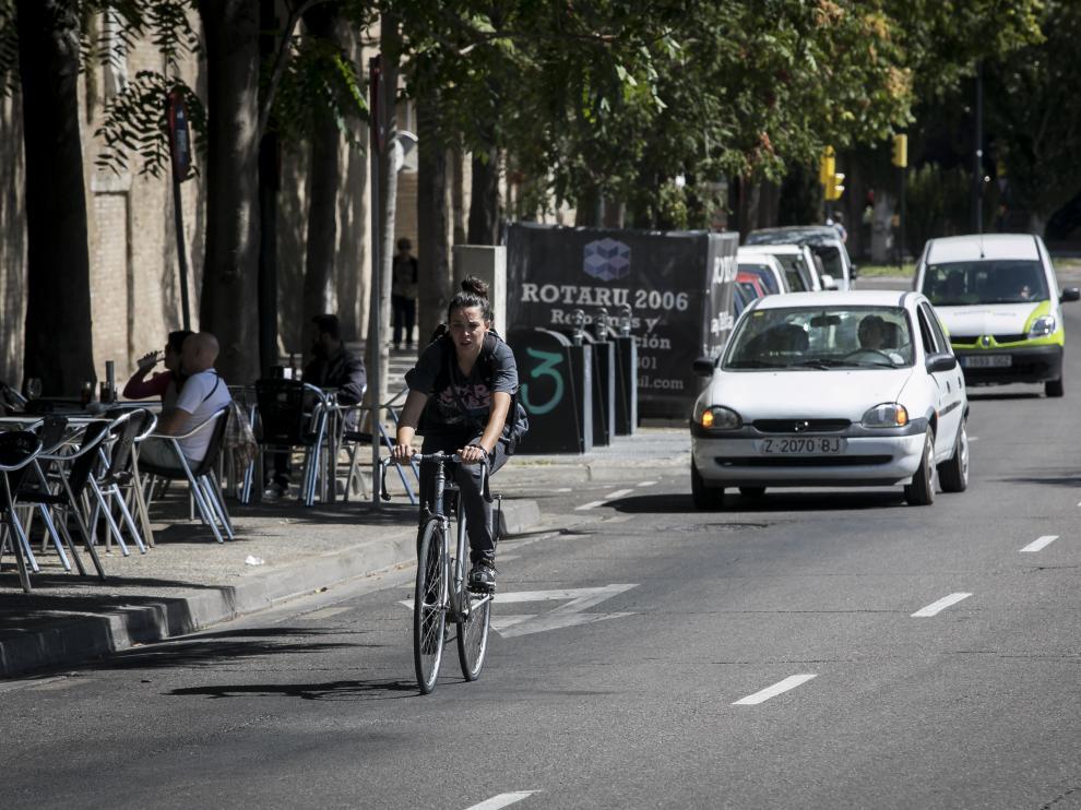 Una ciclista circula entre coches por la calle Asalto.