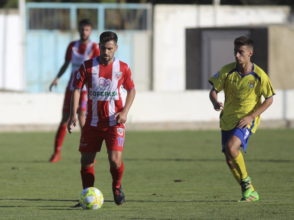 Un jugador del Monzón conduce ante la presión de un rival del Almudévar.