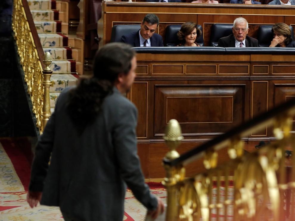 El líder de Unidas Podemos, Pablo Iglesias, pasa ante los miembros del Gobierno Pedro Sánchez (4d), Carmen Calvo (3d) y los ministros Josep Borrell (2d) y Dolores Delgado (d)