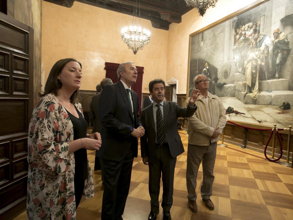 Luis Felipe junto a Jorge Azcón y los concejales de Huesca María Rodrigo y José María Romance en el salón del Justicia, con el célebre cuadro de la Campana de Huesca.