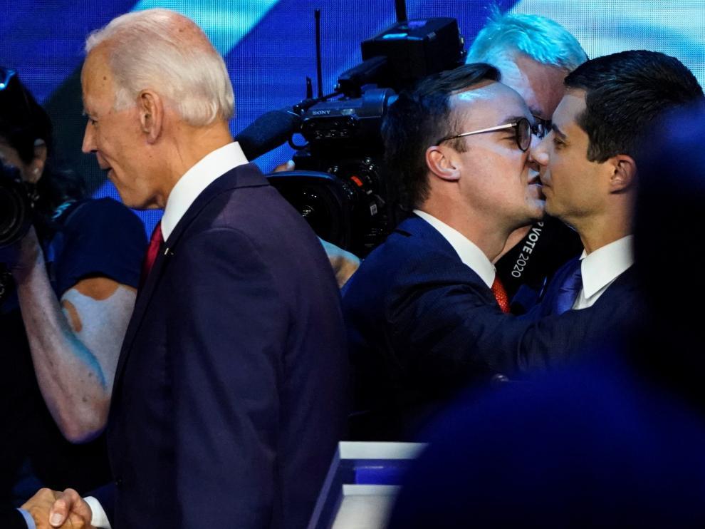 Pete Buttigieg recibe un beso de su marido Chasten con Joe Biden en primer término