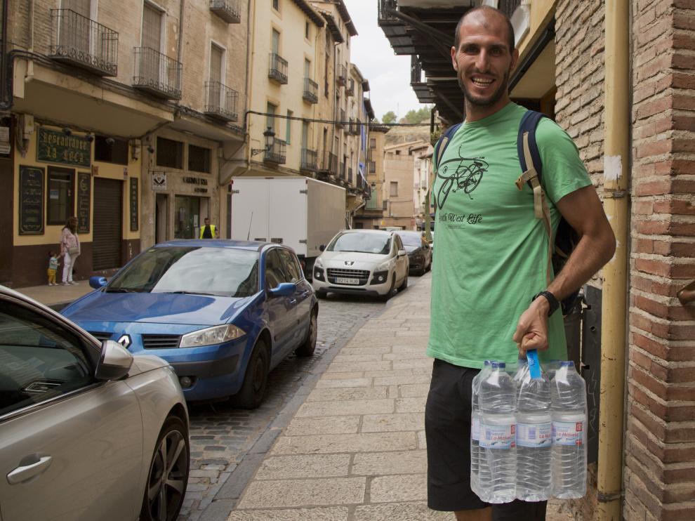 Un vecino, con seis botellas de agua que adquirió en Daroca.