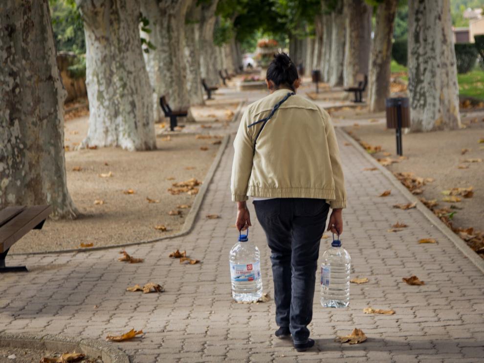 Una mujer camina por Daroca con dos garrafas de agua.