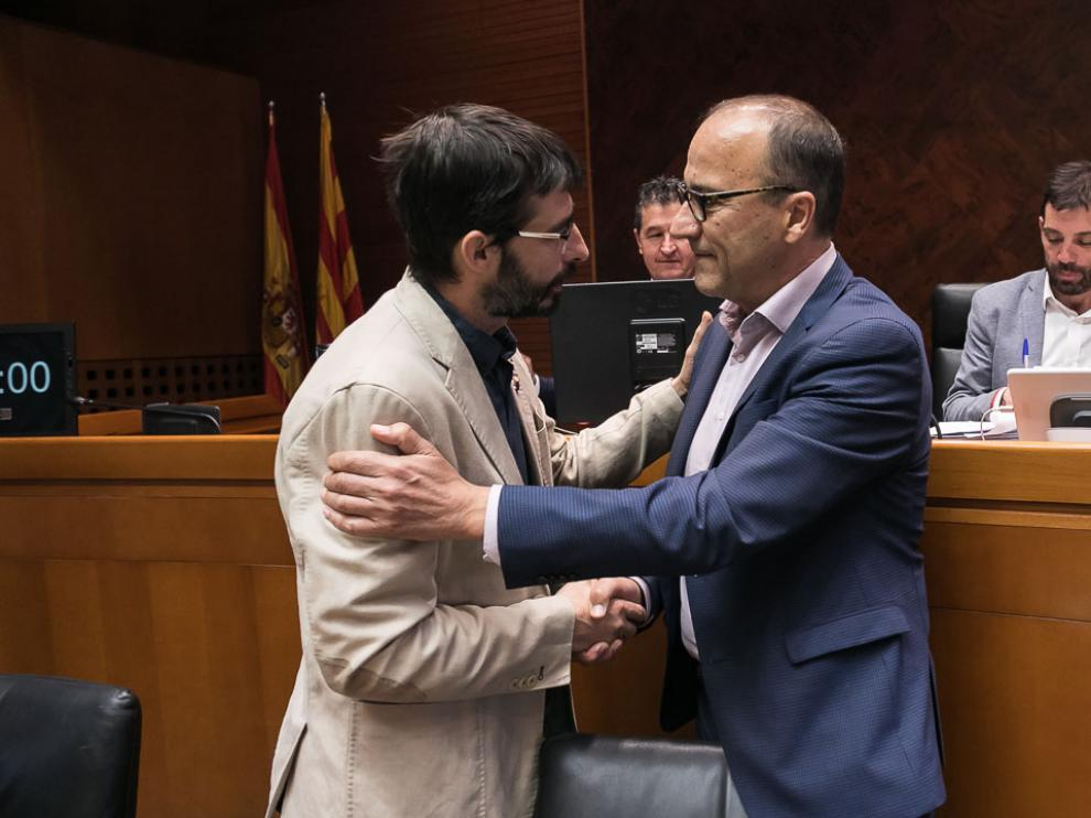Felipe Faci, a .la derecha, saluda a un miembro de la comisión de Educación de las Cortes ante la que ha comparecido este martes.