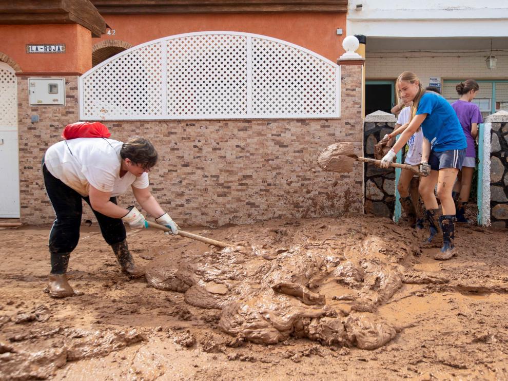 Vecinos de Los Nietos, en Cartagena, limpiando el barro que dejó el temporal de lluvia