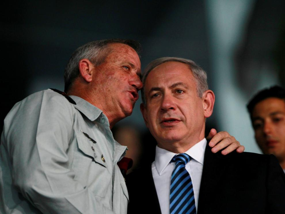 Benny Gantz (i) y Benyamin Netanyahu (d) conversando durante la ceremonia.