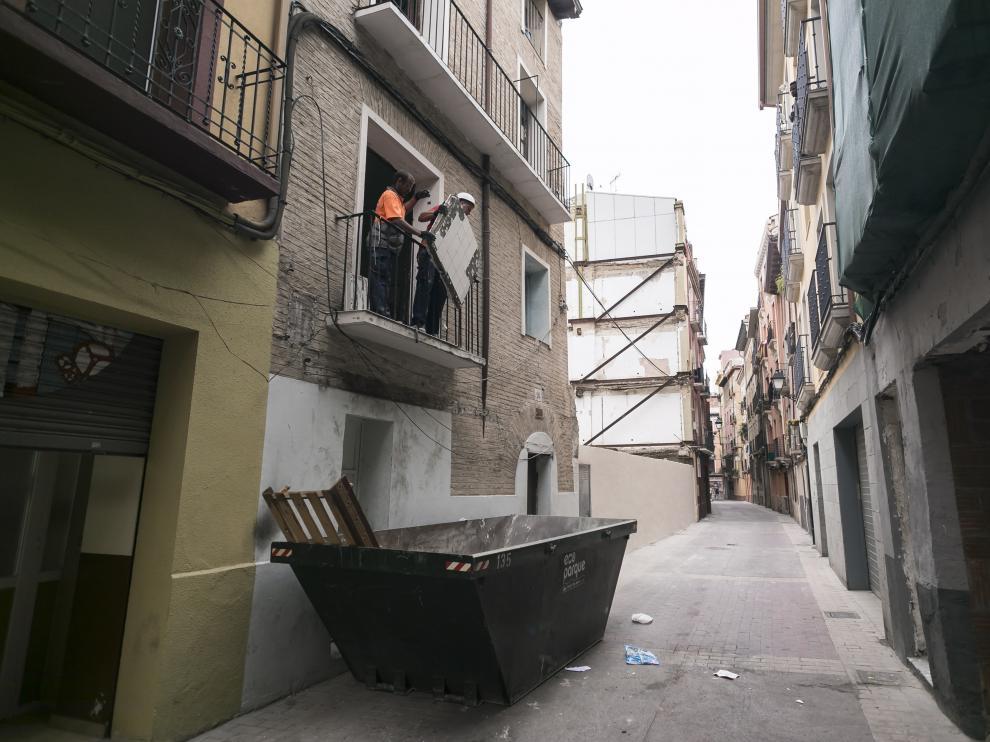 Un obrero arroja al contenedor basura y trastos de la casa okupa de Agustina de Aragón 26.