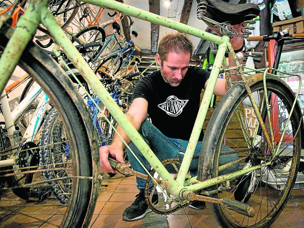 José Manuel Tomé, de La Pomada Bikes, inspecciona una bicicleta para rehabilitarla.