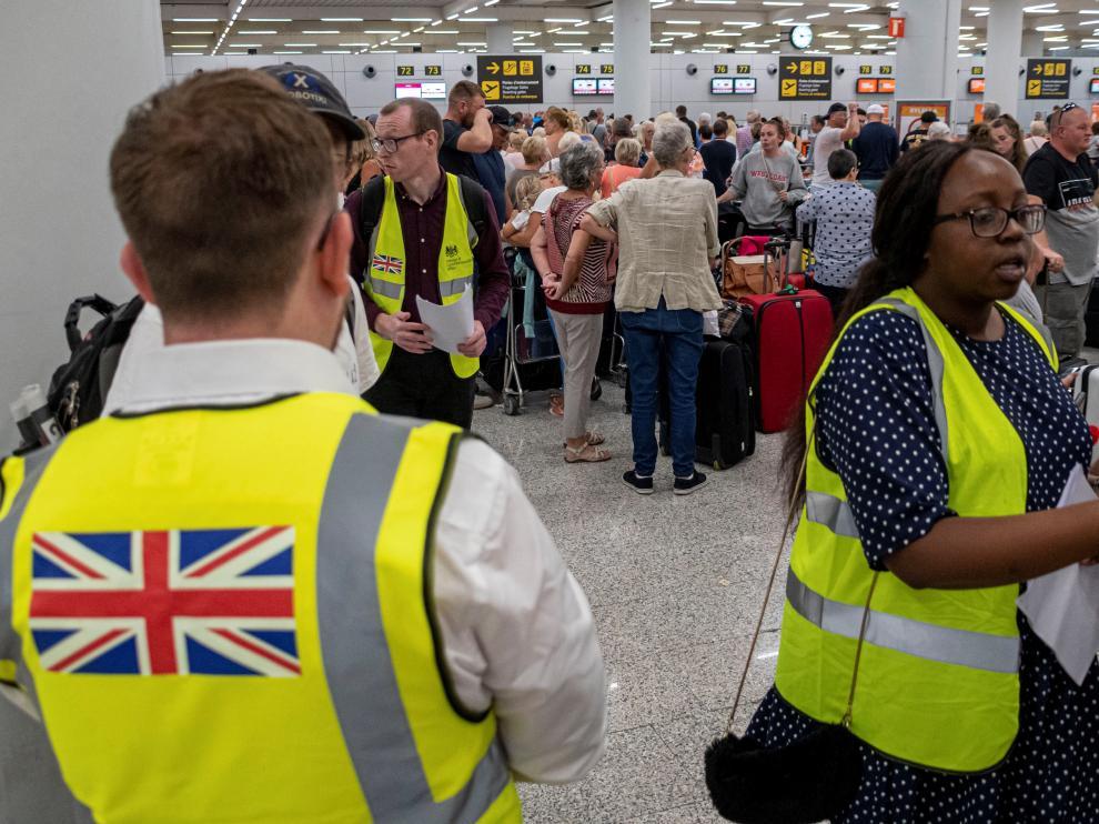 Empleados del Gobierno británico informan a los turistas afectados por la quiebra de Thomas Cook en el aeropuerto de Palma de Mallorca, este lunes.