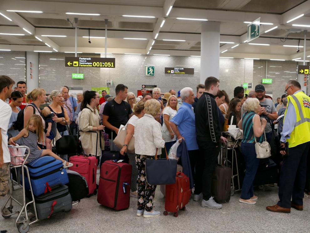 Largas filas de pasajeros y clientes de la agencia de viajes Thomas Cook en el aeropuerto de Mallorca tras el cierre de la compañía.