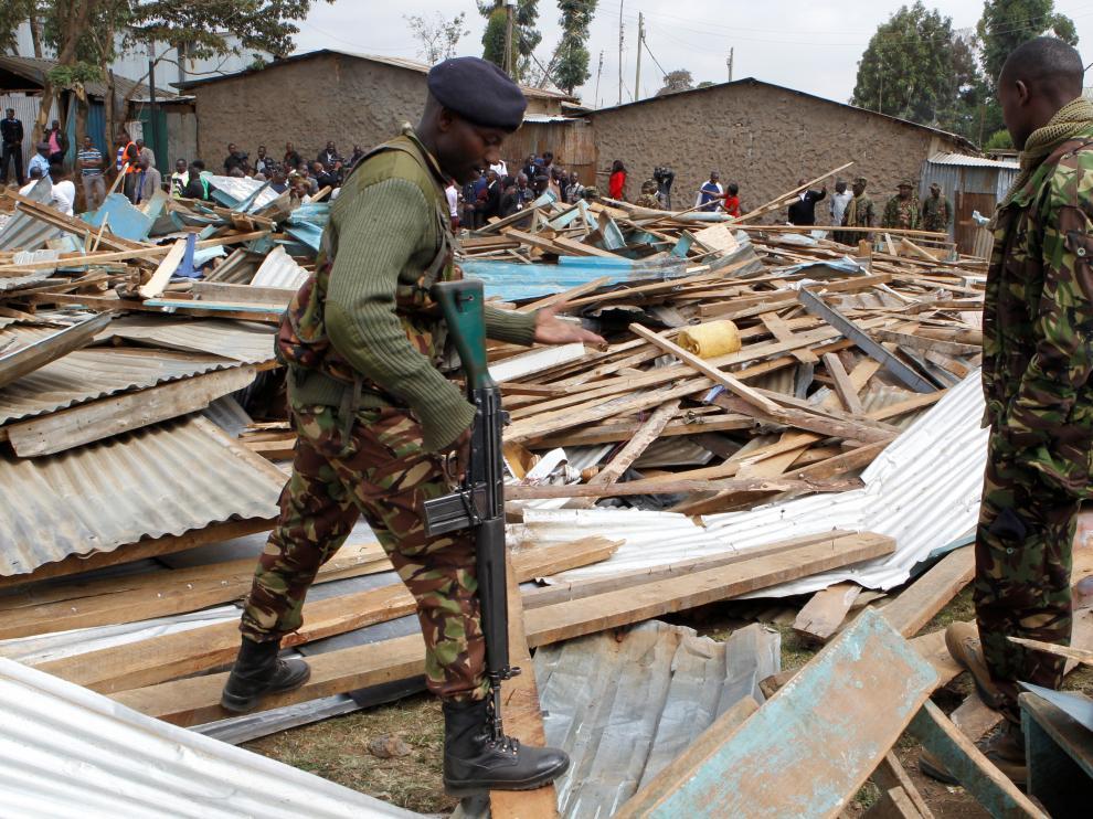 Police officers stand on the debris of a collapsed school classroom, in Nairobi, Kenya, September 23, 2019. REUTERS/Njeri Mwangi [[[REUTERS VOCENTO]]] KENYA-SCHOOL/