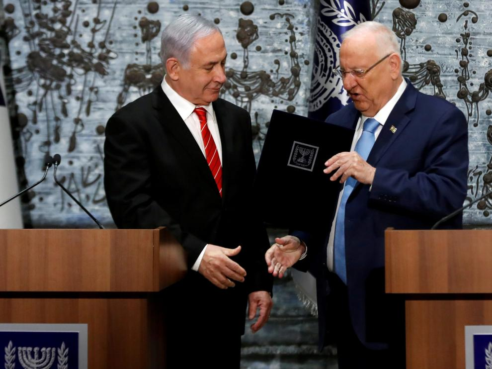 Israeli President Reuven Rivlin gives Israeli Prime Minister Benjamin Netanyahu a file during a nomination ceremony at the President's residency in Jerusalem September 25, 2019. REUTERS/Ronen Zvulun [[[REUTERS VOCENTO]]] ISRAEL-ELECTION/