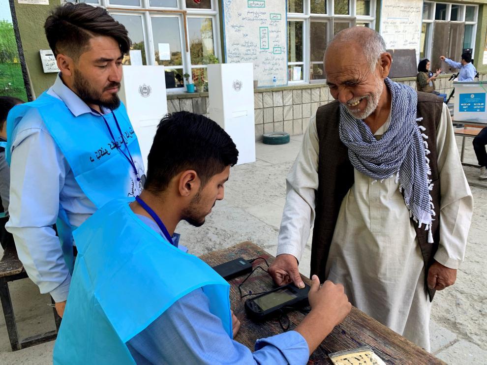 Un afgano que acude a votar intenta sin éxito que la máquina biométrica registre sus huellas dactilare