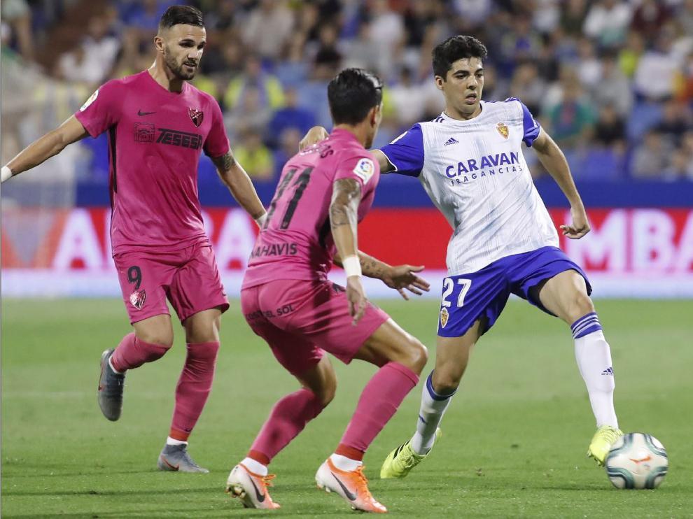 Quique Clemente, con el balón ante Renato y Sadiku este jueves en el partido ante el Málaga en La Romareda.