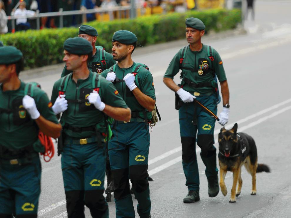 El cabo Sergio Ona, al final del grupo, con la cruz al mérito ya colgada, desfilando este domingo junto a los compañeros del Servicio de Montaña y llevando al perro de rescate Arnold.