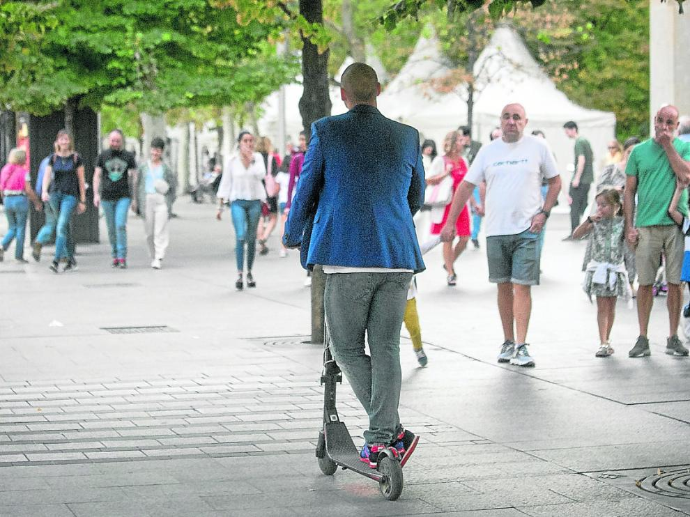 Un usuario de patinete circula de forma irregular por la acera de la plaza de Aragón.