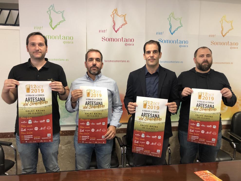 Javier Román, de cerveza Bachiella, el alcalde Jorge Gracia, el presidente de la Comarca, Daniel Gracia y Jorge Zanuy, del restaurante L' Usuella posan con el cartel.