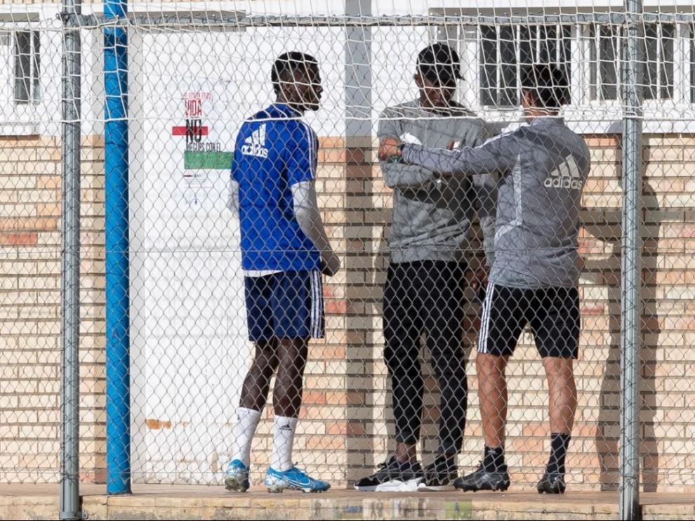 Dwamena, en el centro de la fotografía, con gorra negra y vestido de calle, charla con Bikoro y un auxiliar del Real Zaragoza en la mañana de este miércoles en la Ciudad Deportiva.