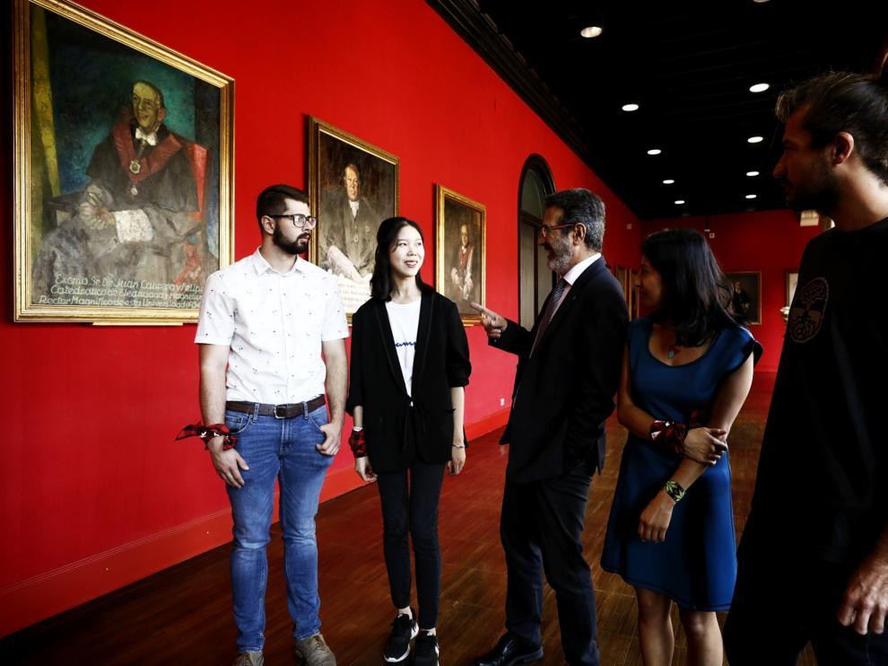 El vicerrector Francisco Beltrán, con cuatro alumnos extranjeros, en el Aula Magna del Paraninfo.