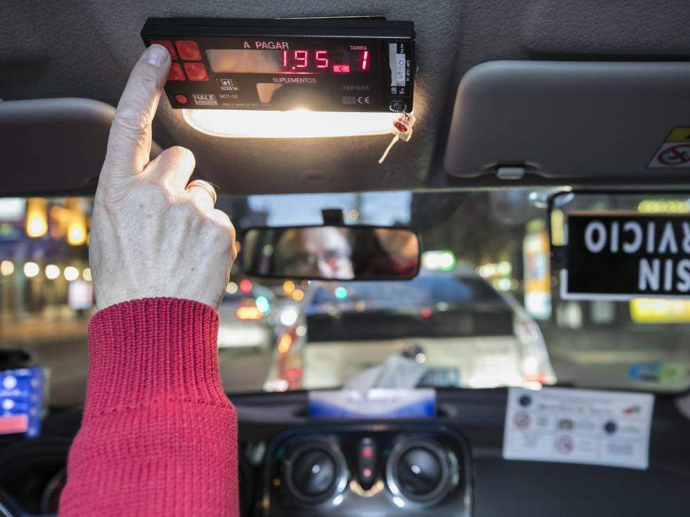 Un taxista activa un contador en el interior de su vehículo.