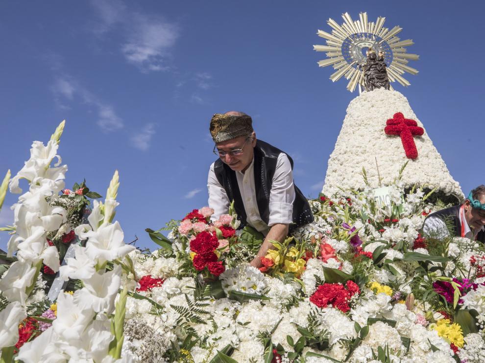 Jardineros trabajando en la confección del tradicional manto de flores de la Virgen en la plaza del Pilar de Zaragoza.