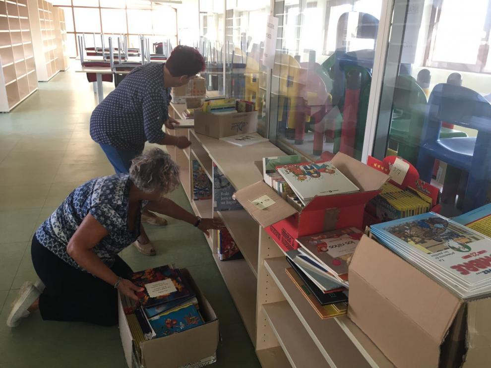 Dos voluntarias ordenan algunos de los libros infantiles en las nuevas instalaciones.