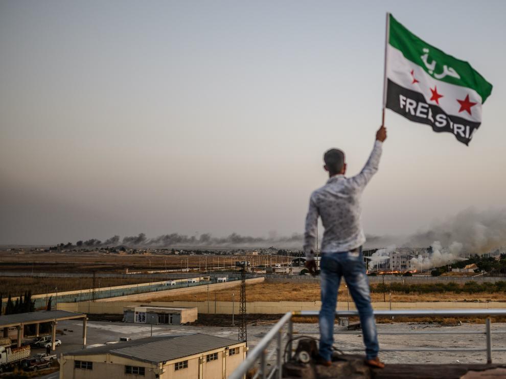 Un ciudadano sirio ondea una bandera del país en la frontera con Turquía