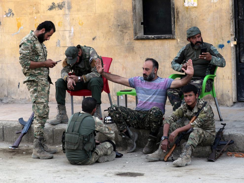 Rebeldes sirios apoyados por Turquía sentados cerca de un puesto fronterizo