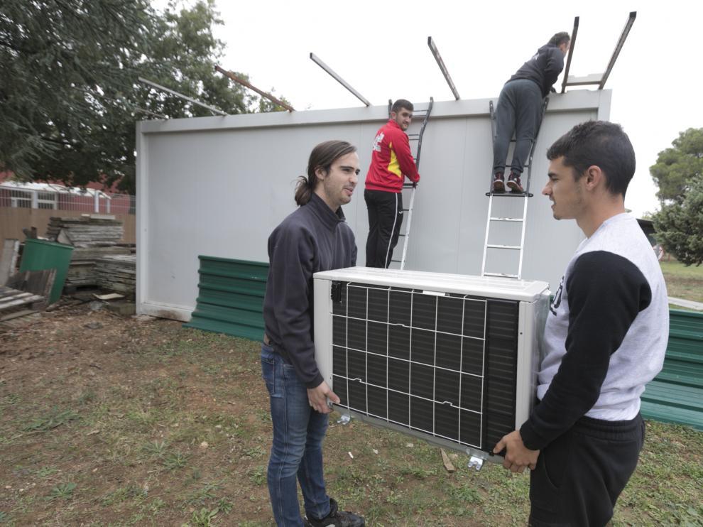 Alumnos del centro de FP Pirámide de Huesca, el pasado viernes, instalan equipos de climatización en el aula de experimentación.