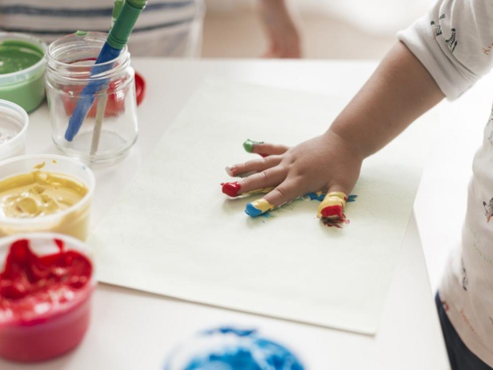 Un niño pinta con las manos.