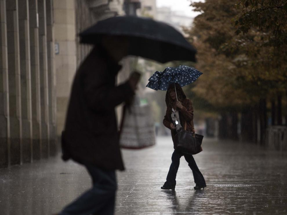 Dos personas se protegen de la lluvia en Zaragoza