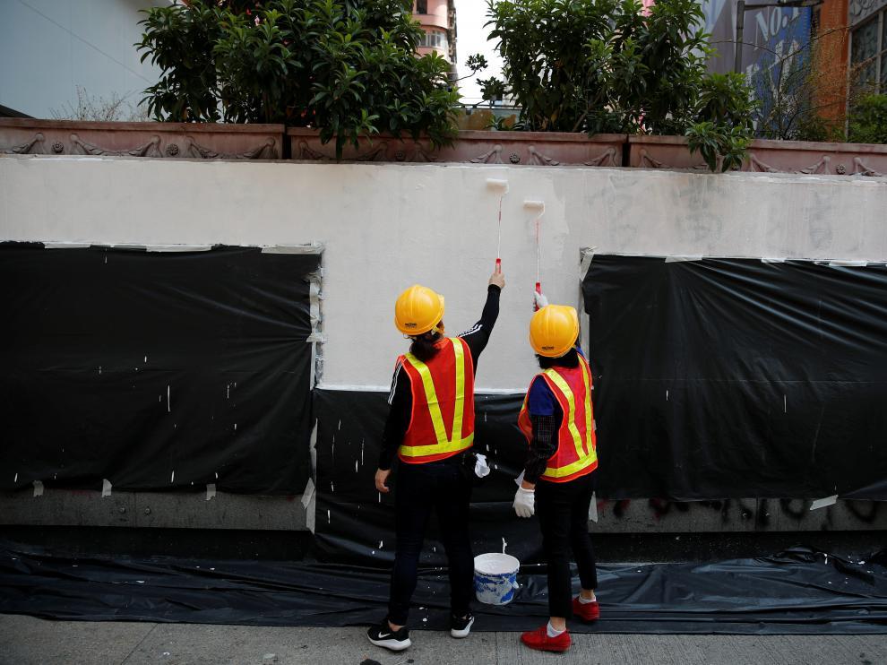 Dos trabajadores adecentan una fachada con pintadas tras una manifestación en Hong Kong