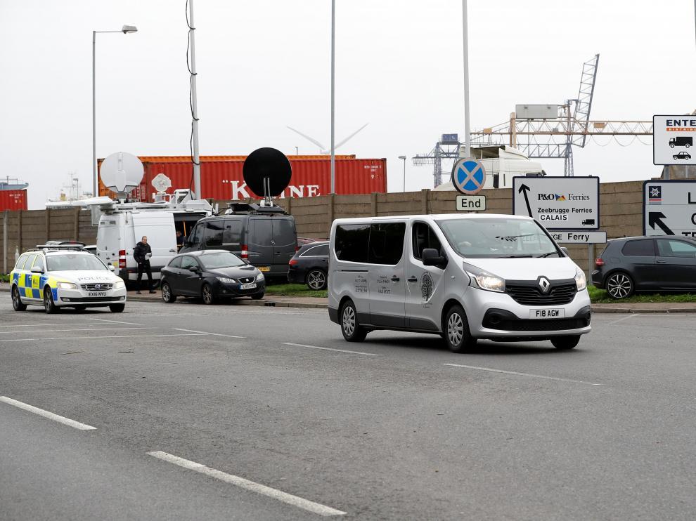 Un furgón fúnebre abandona el puerto de Tilbury escoltado por la Policía.