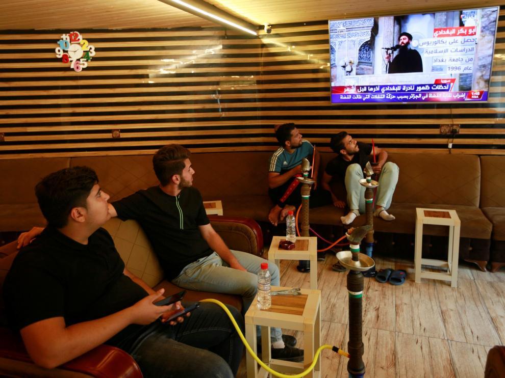 Jóvenes iraquíes siguen por televisión la noticia de la muerte de Al Bagdadi.
