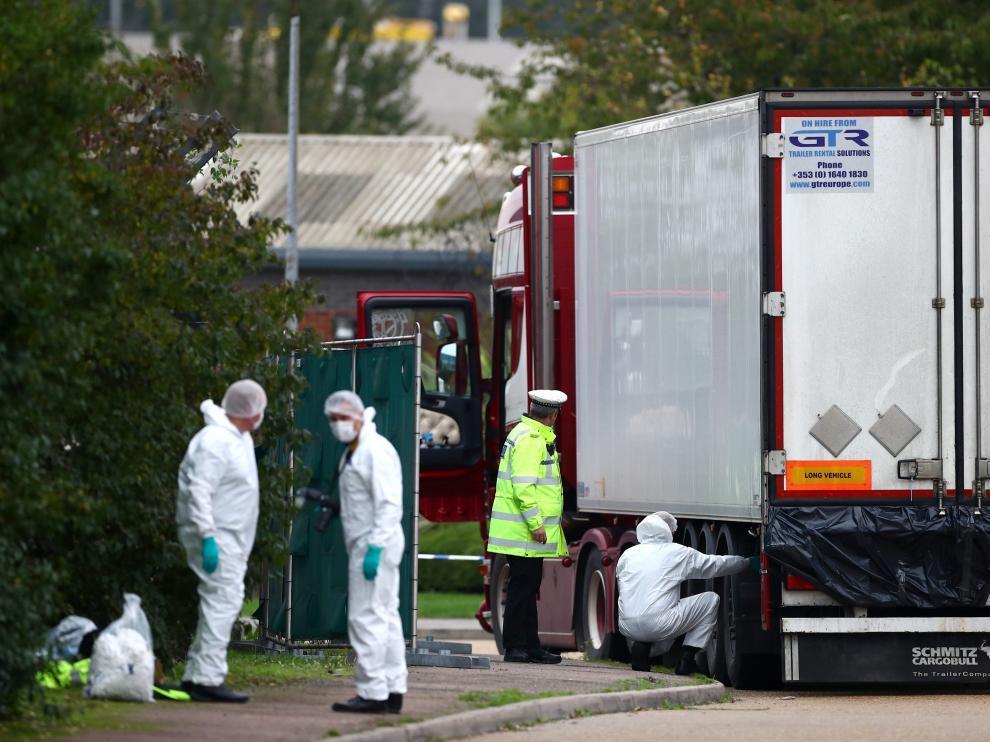 La policía examina el lugar donde fueron encontrados los cuerpos, en el interior de un camión en el Reino Unido